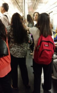 Bag-carrying ladies crowd the train.